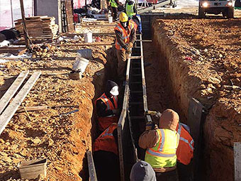 Workers Setting Up Concrete Form in Trench